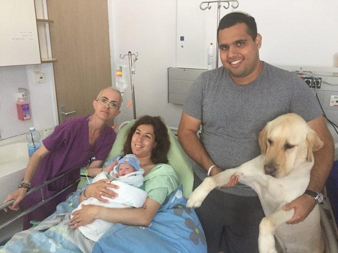בת אל ושגיא עם התינוק, הכלב ניאון וצוות חדר הלידה (צילום:אפרת שררה ואופיר לוי, בית החולים קפלן)