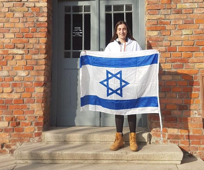 טל אנגל עם דגל ישראל ליד בלוק 27 באושוויץ