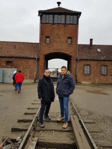 זוהר בלום ויניב מרקוביץ' על רקע מחנה אושוויץ