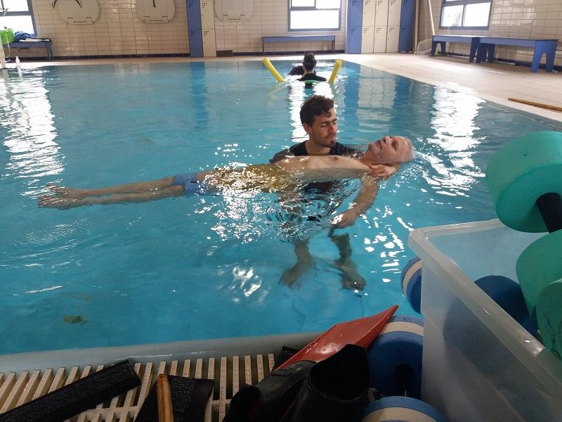 המטפל יואב בן -צבי עם המטופל אלי פורת בבריכה הטיפולית של חוויות (צילום: מוטי שודריך)