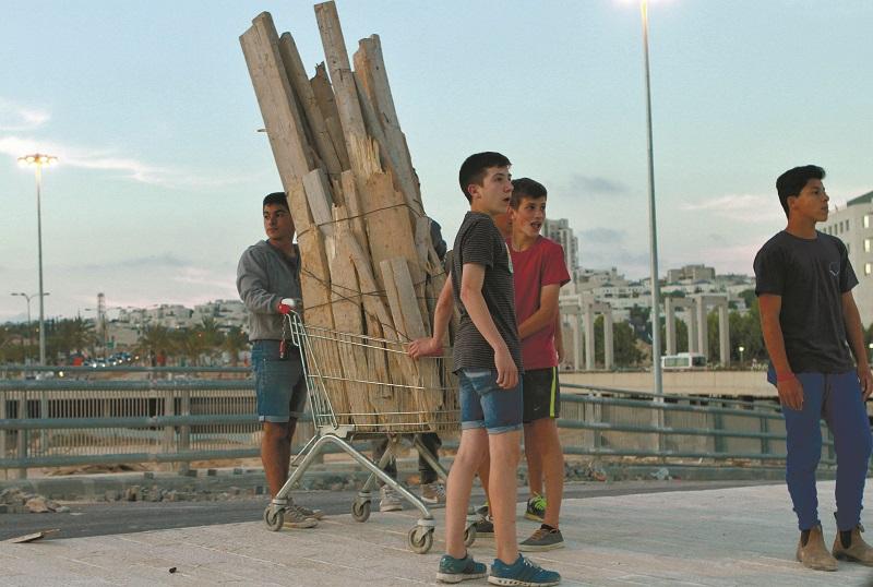 """ילדים אוספים קרשים לל""""ג בעומר (צילום אילוסטרציה: גיל כהן-מגן)"""