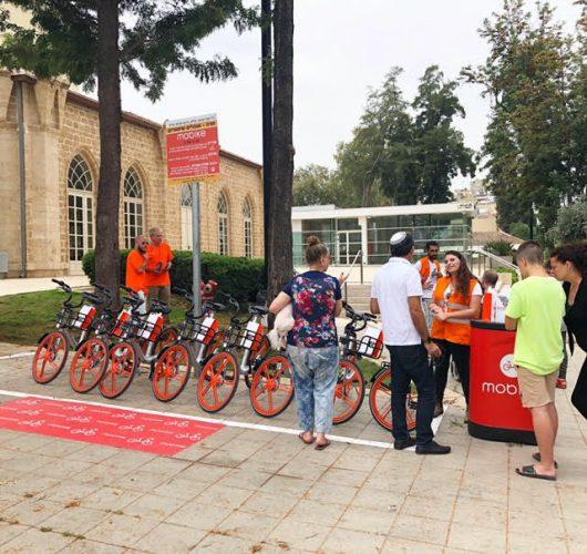 תושבים מקבלים הסבר על האופניים השיתופיים