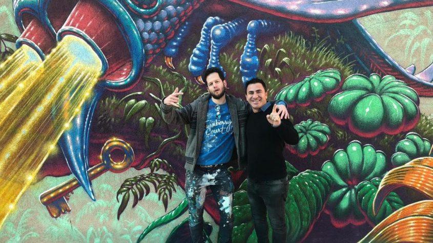 """משמאל: דניאל פילוסוף וגולן ביטון על רקע ציור הקיר במתנ""""ס קרית משה"""