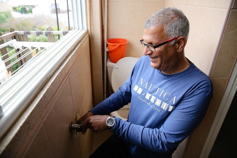 אב הבית אלי מאיר בעת התקנת ידית בשירותים בביתו של חבר קהילה תומכת (צילום: נגה שדמי ואן דה ריפ)
