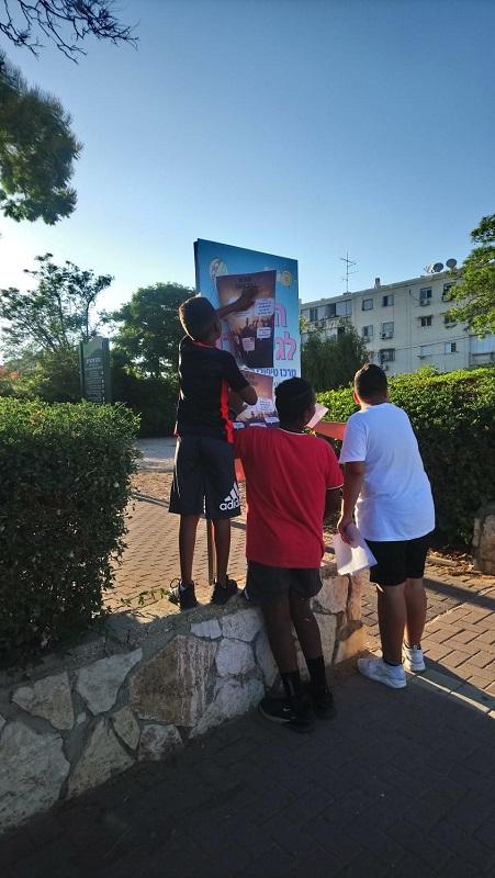 ילדים מקרית משה תולים שלטי פרסום לקראת ליין הפעילות הקיצית