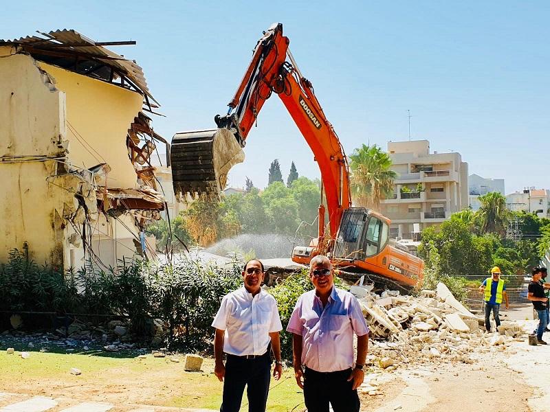 משמאל: זהר בלום ואבי קיש על רקע הריסת מבנים ישנים בקרית החינוך דה שליט