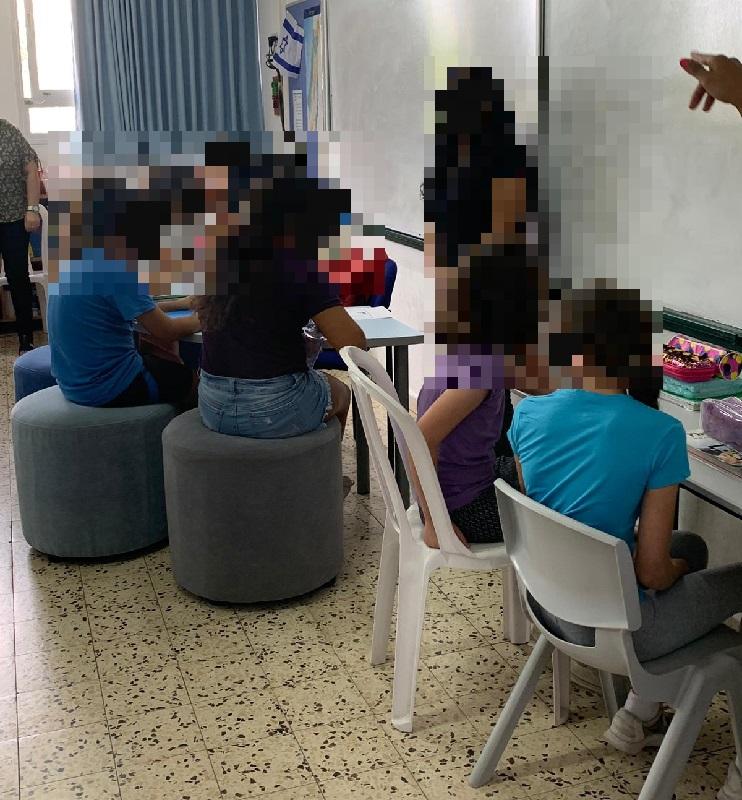 תלמידים בבית הספר ויצמן יושבים על פופים ובצמוד לקיר