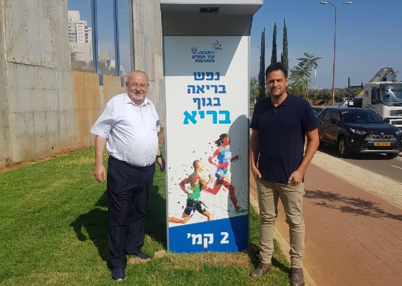 משמאל: רחמים מלול ויניב מרקוביץ׳ ליד שלט סימון מרחק בציר מנחם בגין